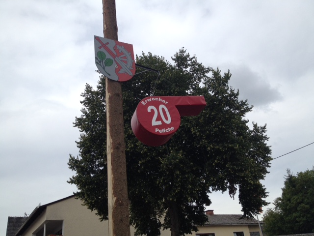 Große rote Trillerpfeife als Hausnummerbeschriftung an Pfahl befestigt, an welchem ein Familienwappen hängt. Im Hintergrund ein Baum und Häuser unter grauem Wolkenhimmel