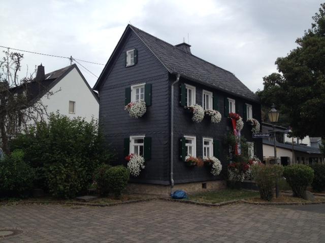 Graues Haus mit vielen Fenstern, vor denen überall weißblühende Blumen aus Blumenkisten wachsen, unter grauem, bewölktem Himmel.