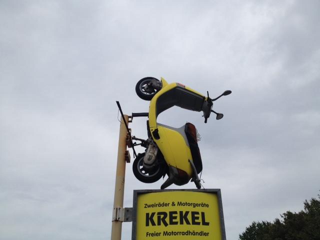 Ein Richtung Himmel fahrender gelber Roller als Deko und Werbung für ein Zweiradgeschäft namens Krekel vor graublauem bewölktem Himmel