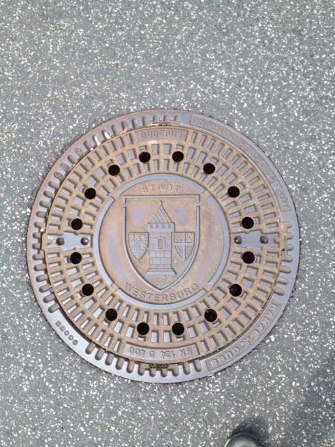 Gullydeckel in Westerburg mit dem Wappen der Stadt, ringsum Teer,