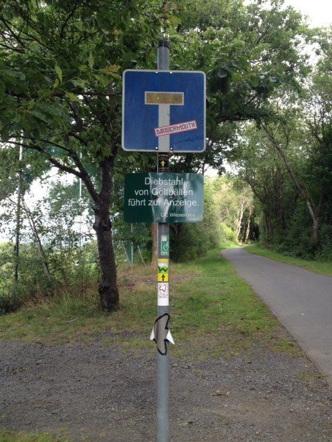 Sackgassenverkehrschild vor Radweg. Unter der Sackgassentafel steht eine Warnung weiß auf grün: Diebstahl von Golfbällen führt zur Anzeige.