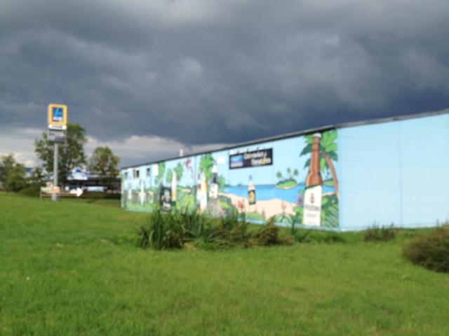 Gewitterdunkler Wolkenhimmel über hellblauem Gebäude, das mit Strandszene bemalt ist. Im Vordergrund Wiese, hinten eine Discounterwerbung.