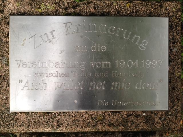 Erinnerungstafel aus Metall auf Stein, die zwei Parteien an eine Vereinbarung aus dem Jahre 1997 erinnern soll.