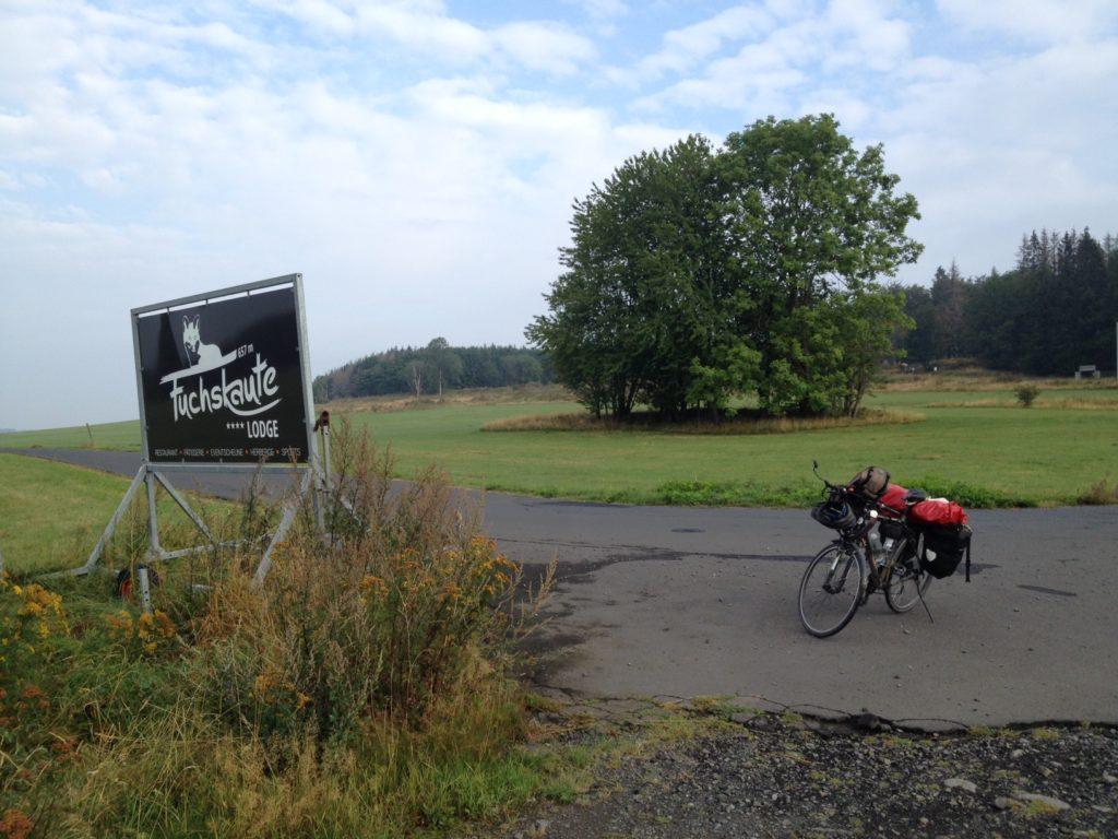 Rechts im Bild das Reiserad auf der Straße, im Hintergrund Wiese und Bäume, links im Bild eine Infotafel zur Fuchskaute-Lodge, eine Restaurant auf der Passhöhe