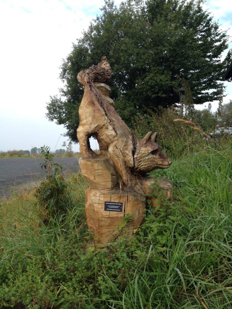 Ein grob mit der Kettensäge geschnitzer Fuchs in einer Anpirschhaltung auf Holzsockel mit Infotäfelchen, im Hintergrund links die Straße, rechts Wiese und Bäume