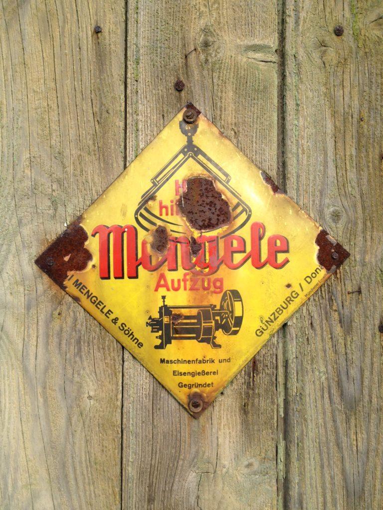 Rostiges, quadratisches, auf Eck stehendes Metallschild. Grudnfarbe gelb, mit rotem Logo der Aufzüge-Firma Mengele mit Infos am Rand in schwarzer Schrift. An Holzwand geschraubt.