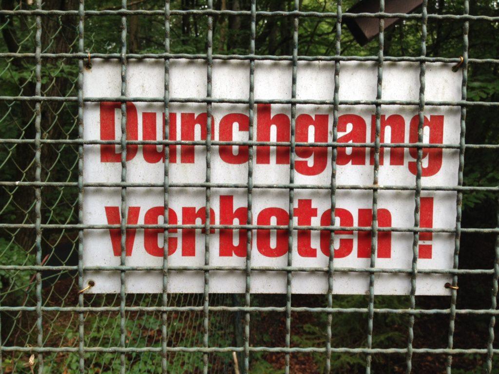 Durchgang Verboten-Metalltafel in roter Schrift auf weißem Grund hinter einem grobmaschigen Gitterzaun.