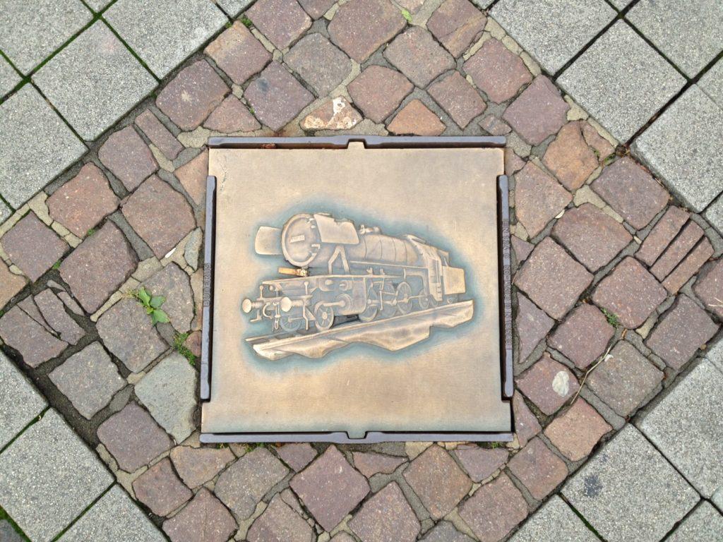 Quadratischer, kupferfarbener Gullydeckel inmitten von Pflastersteinen, der eine alte Lokomotive abbildet