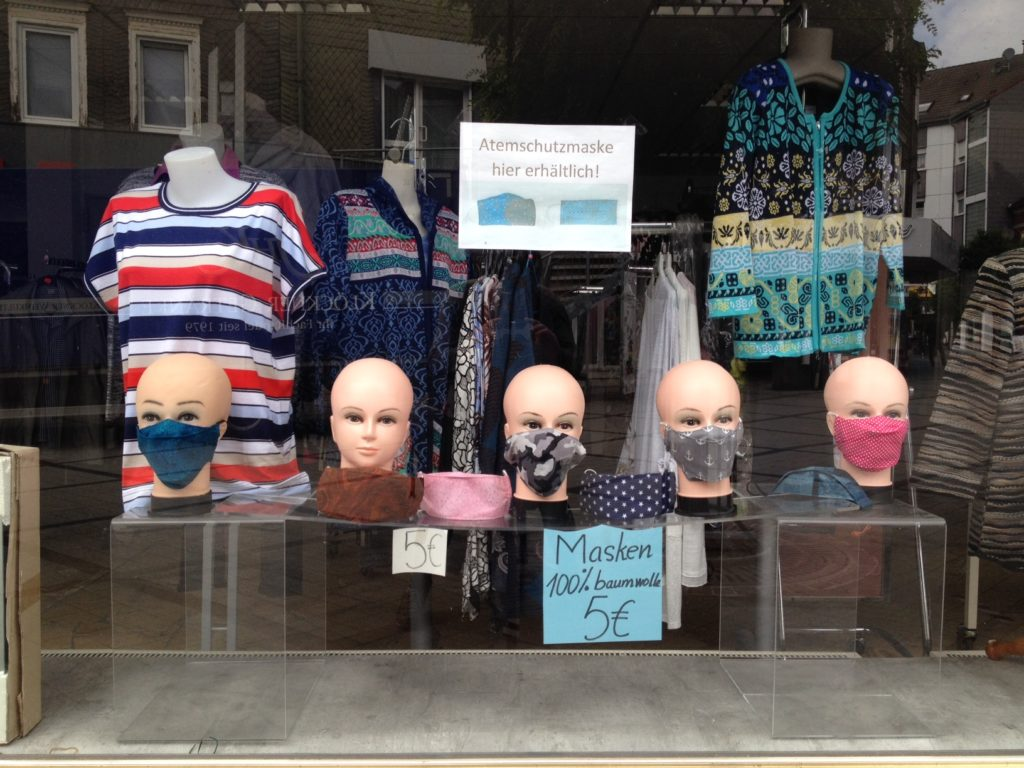 Schaufenster eines Kleiderladens. Im Vordergurnd fünf Schaufensterpuppenköpfe mit Mund-Nasen-Schutzmasken aus Baumwolle, die auf einem Schild für fünf Euro angeboten werden.