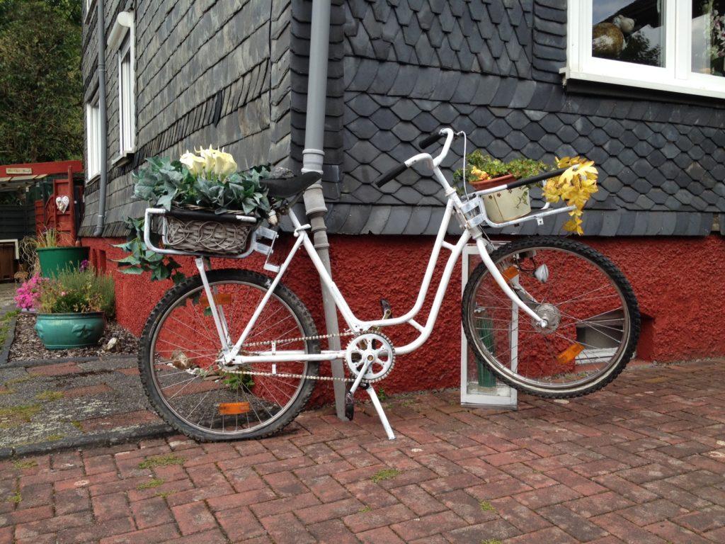 Ein weiß bemaltes Fahrrad mit platten Reifen, das mit je einem Korb hinten und vorn mit Pflanzen dekoriert ist. Vor einem Haus mit fuchtroten Mauerwerk unten und dunkelgrauen Schindeln darüber.