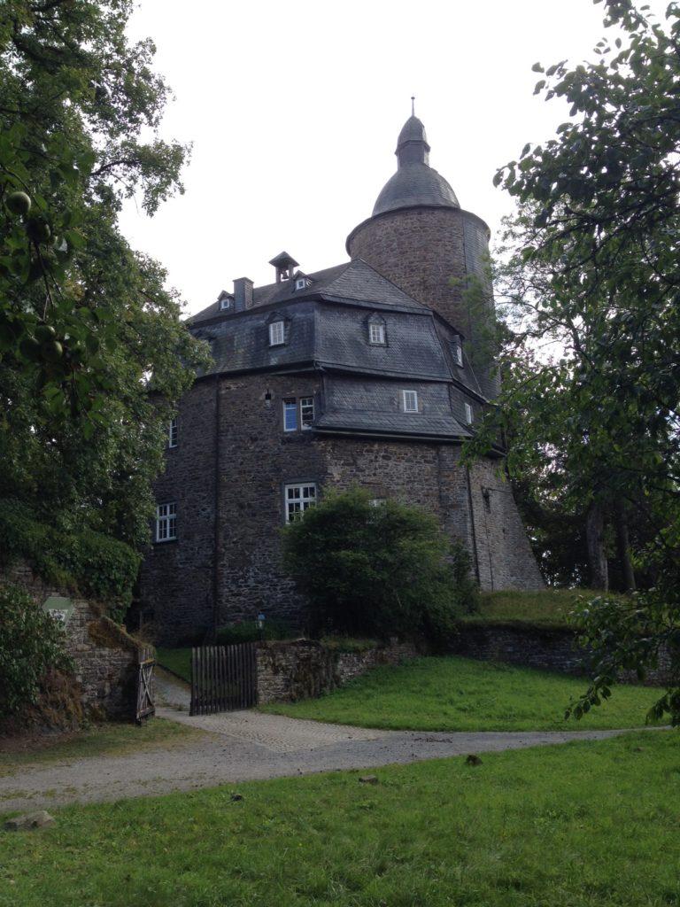 Mittig im Bild eine aus dunkelrotem Naturstein erbaute Burg, umgeben von Bäumen, Sträuchern und Wiesen.