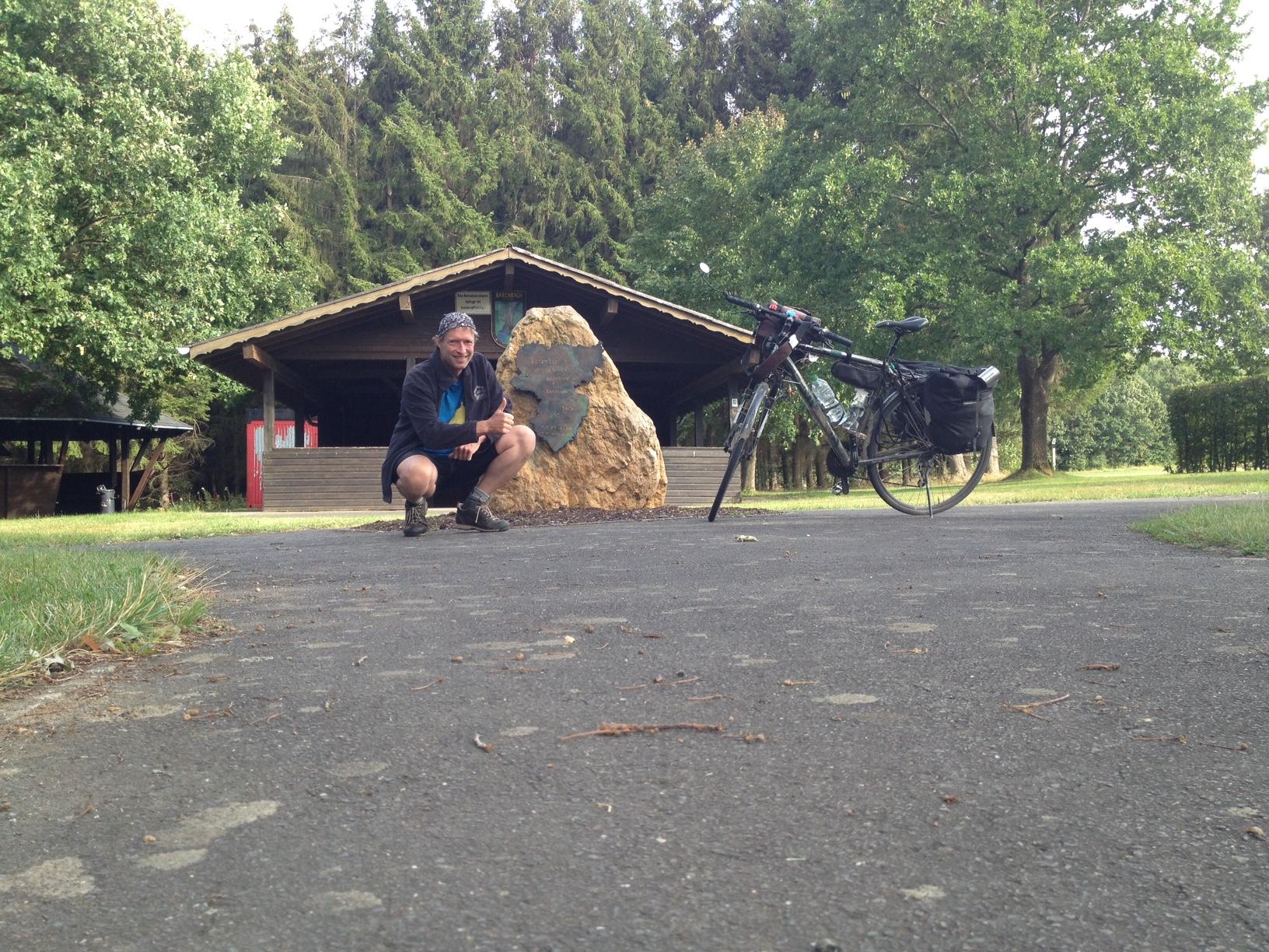 Untere Bildhälfte Teerboden. Obere Bildhälfte: Künstler hockt neben dem Mittelpunkt-Stein. Daneben steht sein Fahrrad. Im Hintergrund Waldhütte und Bäume.
