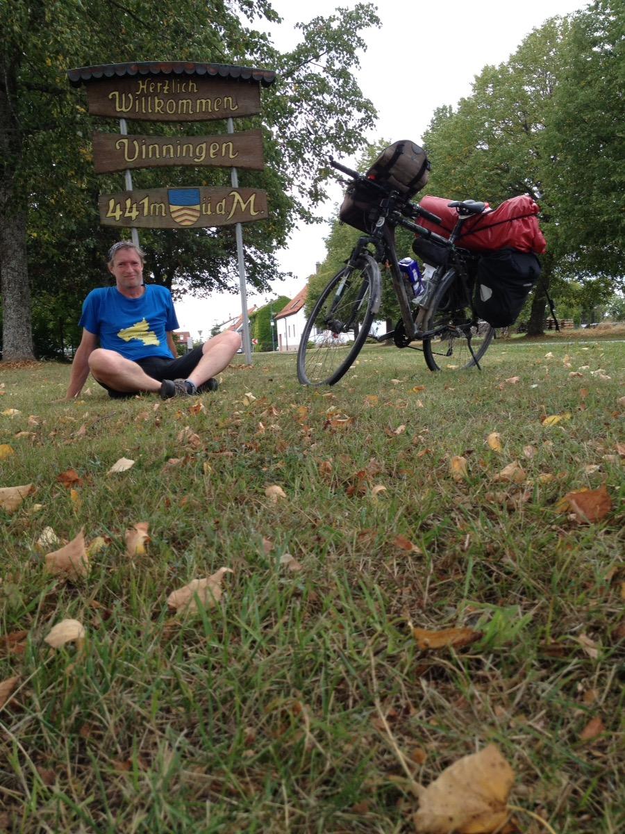 Mann und Fahrrad vor liebevoll geschnitztem Schild Vinningen 441 m über dem Meer