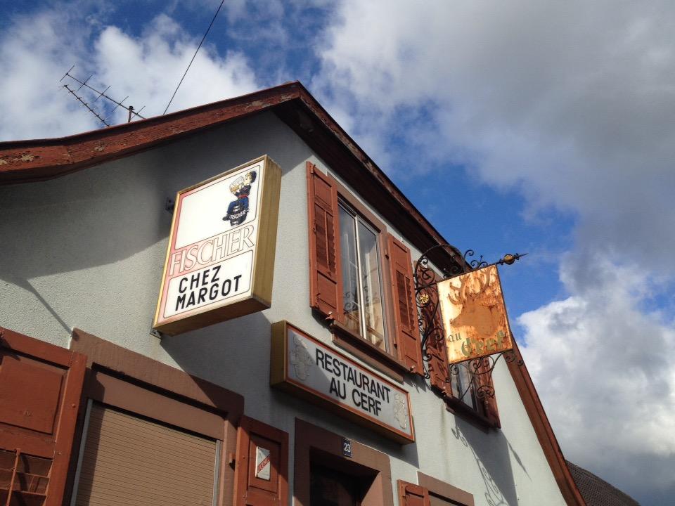 Dachgibel eine Restaurants an der französischen Grenze. Restaurant au Cerf steht auf einer vergilbten Tafel, auf einer anderen Fischer und Chez Margot. Über dem Gibel dichtwolkiger Blauhimmel.