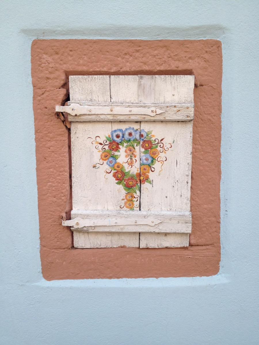 Mit Bauernmalereiblumen in rot-blau-orange-Tönen bemalter, rosa grundierter Fensterladen, in einer blaustichig-weißen Wand. Der Laden ist orange umrahmt.