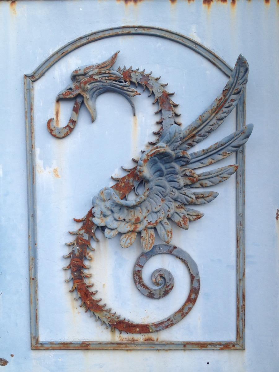Rostiger Seepferddrache aus Metall auf hellblauem Metalltor oder -laden.