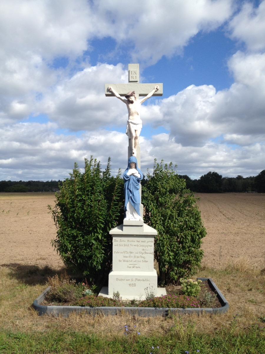 Steinernes Kruzifix auf Steinsockel mit einer blaugewandeten Maria in stehender Gebetshaltung unter dem Kreuz. Dahinter ein Gebüsch und darüber ein dramatisch bewölkter Blauhimmel.