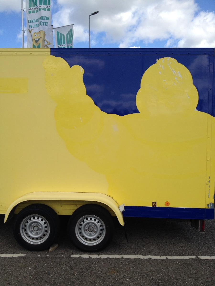 Lastwagen-Seitenfront in den Farben Gelb und Blau bemalt. Stilisierte Umrisse einer Comicfigur.