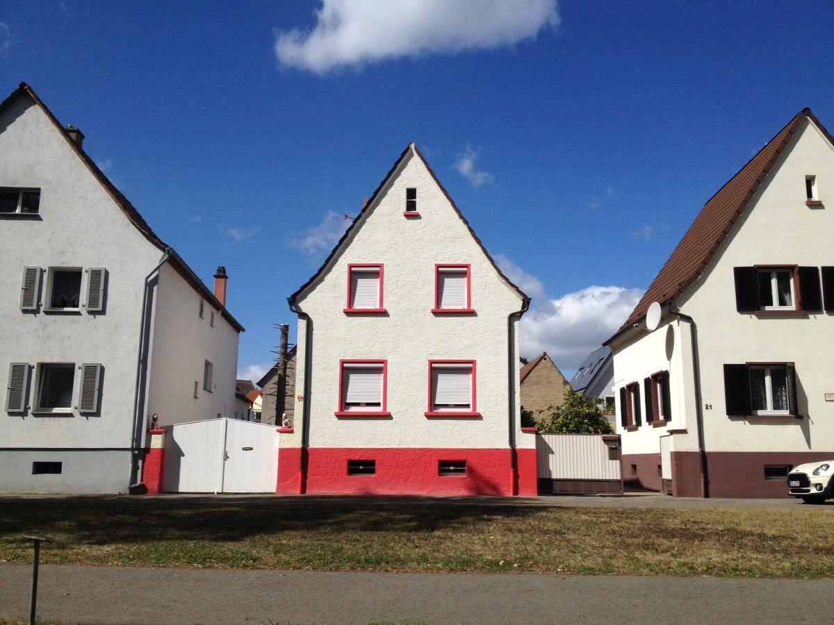 Drei nebeneinanderstehende Spitzgibelhäuser. Das Mittlere mit roten Zierelementen, die andern beiden grau respektive braun. Darüber Blauhimmel.