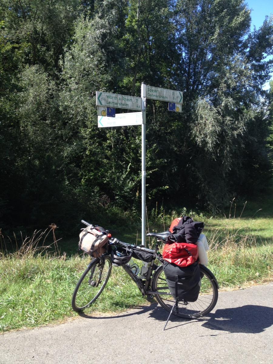 Das Reiserad steht an einem Wegweiser der nach Wörth links und nach Speyer rechts zeigt. Im Hintergrund Bäume und Wiese.
