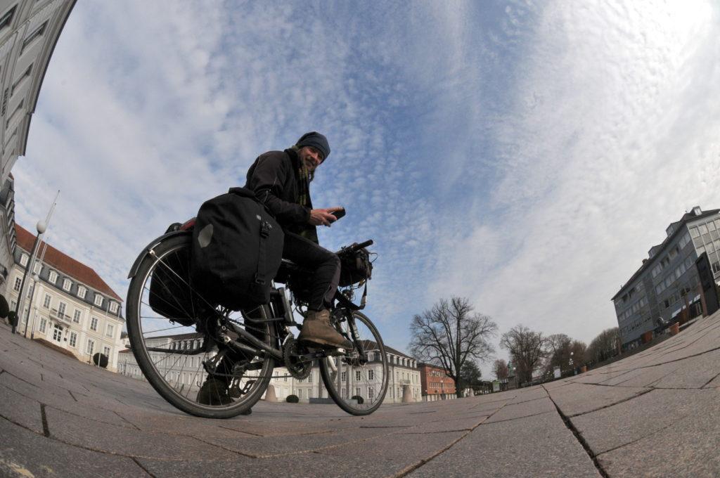 Fischaugenaufnahme 'underfoot' Radler mit Winterkleidung vor barocken weißen Gebäuden auf weitläufigem Platz