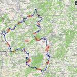 Landkarte mit einer Linie, die der Kontur von Rheinland-Pfalz nahe kommt. Verschiedene Markierungen in blau und rot zeigen Regionen, in denen die Tagesetappen der fünfzehntägigen Radreise markiert sind.