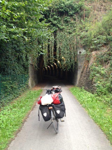 Das Reiserad steht mittig auf einem Radweg, der in der Bildmitte in einen gut beleuchteten Tunnel führt. Rechts und links und über dem Tunnel ist es grün: Wiese, Sträucher, Bäume, Efeu.