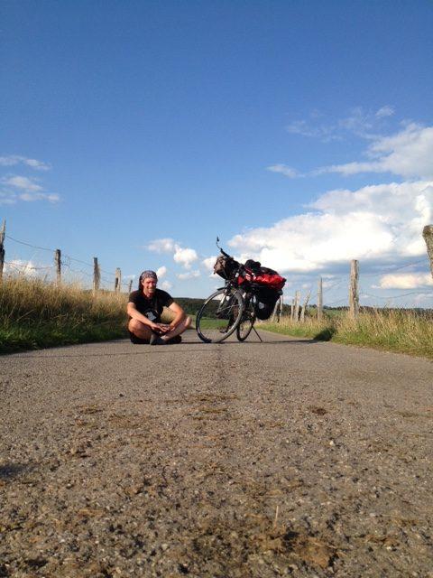 Mann sitzt im Schneidersitz links neben seinem Reiserad auf der Straße. Von unten vorne aufgenommen, so dass vorne viel Straße zu sehen ist. Darüber blauer Himmel mit wenig Wolken. Links und rechts je ein Weidezaun und Wiesen.