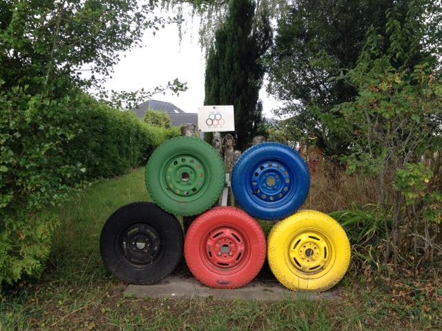 Fünf mit den Olympia-Farben bemalte Autoreifen frontal aufeinander gelegt, unten drei (schwarz, rot gelb), oben zwei (grün und blau). Im Hintergrund eine kleine Erklärtafel. Drumherum Gebüsch, Hecke, Bäume, hinten ein Haus und bleicher Himmel.