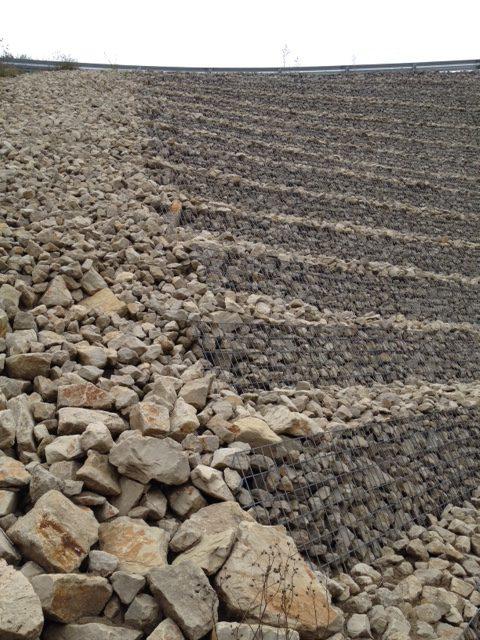 Großes, abschüssiges Geröllfeld mit großen, kantigen Steinen. Am Horizont vereinzelte Bäumchen als feine Silhouetten. In regelmäßigem Abstand sind auf dem Geröllfeld quer zum Hang Gitter gelegt, vermutlich um das Abrutschen der Steine zu verhindern.