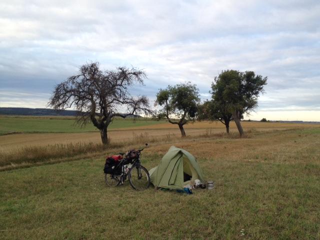 Das Nachtlager auf einer frischgemähten Wiese. Im Hintergrund einzelne Streuobstbäume, im Hintergrund Weide- und Ackerland, am Horizont eine Hügelkette, darüber wolkiger Blauhimmel.