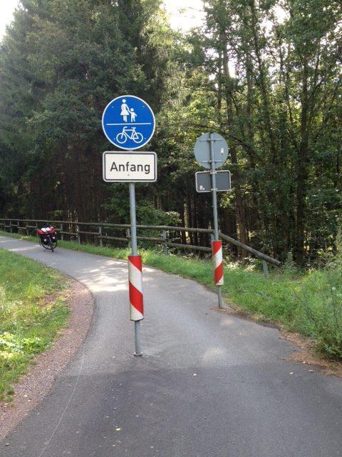 Mit Anfang bezeichnete Rad- und Wanderweg-Tafel mittig vor einem nach hinten links verlaufenden Teerweg, von hinten sieht man eine ähnliche Tafel, die vermutlich das Ende des Weges anzeigt. Rechts und links Wiese, Gebüsch, Bäume.