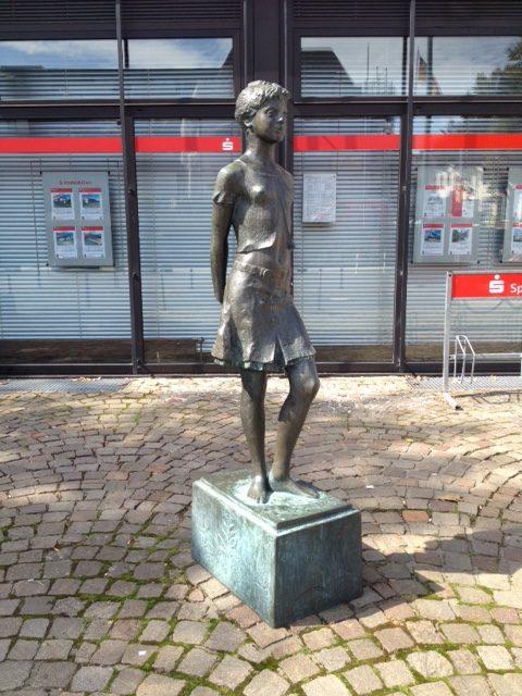 Metallskulptur, die eine junge Frau mit kurzen Haaren und einem kurzen Rock zeigt, die nach rechts vorn guckt. Im Hintergrund ein Geschäftsgebäude mit Rolläden geschlossen. Unter dem Metallsockel der Skulptur ein Kopfsteinpflasterplatz.
