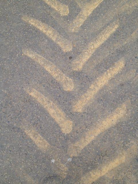Gelbsandige Traktorradspur auf grauem Straßenbelag, nach oben offene V-Formen.