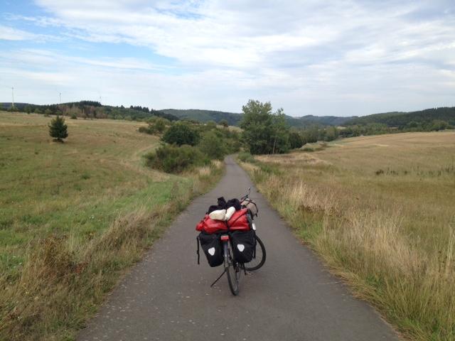 Mittig von vorne nach hinten verlaufender Radweg, rechts und links gelblichgrüne Wiesen, vorne Gebüsche, im Hintergrund Bäume, Wälder, Hügel. Darüber wolkiger Blauhimmel.