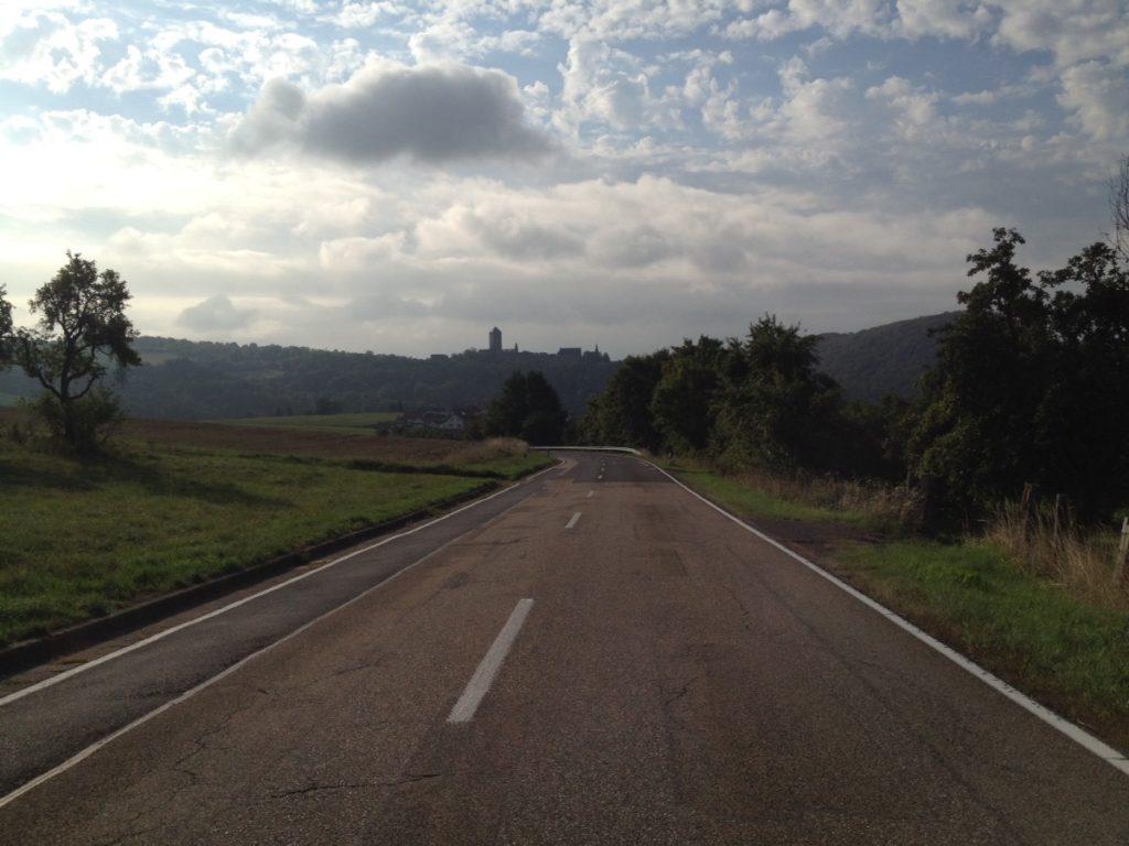 Straßenflucht durch grüne Lande im Gegenlich mit Blick auf die ferne Silhouette einer großen Burganlage. Der Himmel ist dicht bewölkt.