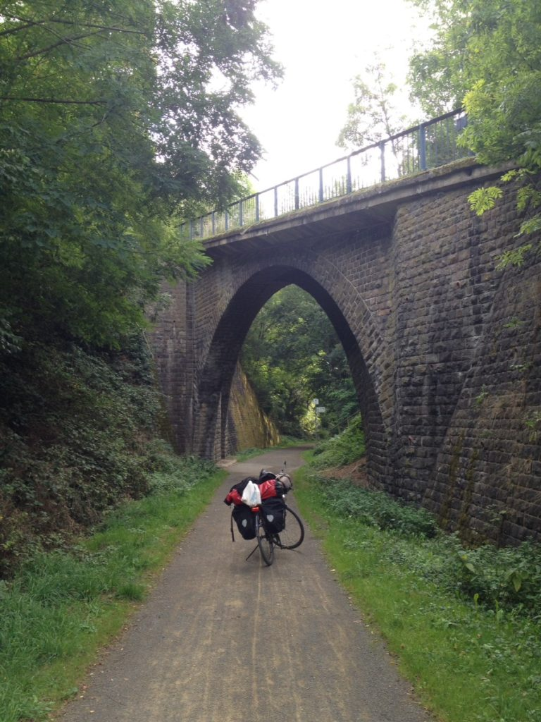 Ein fast spitzer Rundbogen tut sich, durch die Perspektive und die schräge Flucht über einer Bahntrasse auf. Darunter mittig im Weg ein voll bepacktes Reiserad.