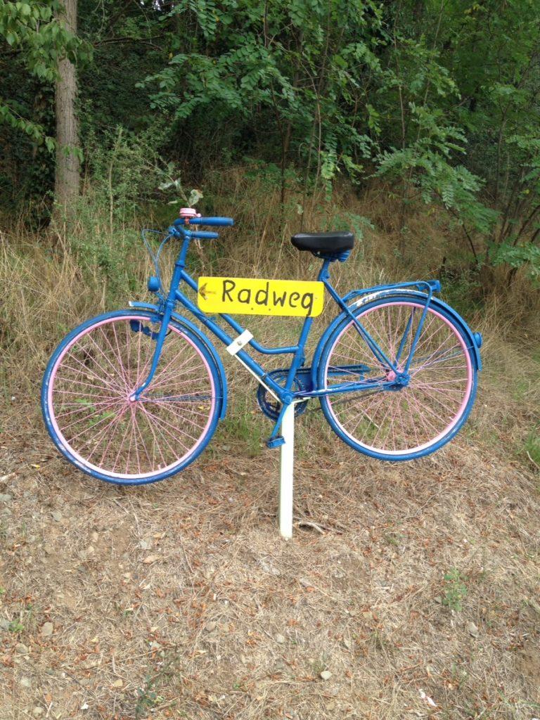 Ein blau angemaltes Dekorad auf Stahlrohr für immer befestigt an einem abgedörrten Hang, daran ein gelbes Schild mit der Aufschrift Radweg