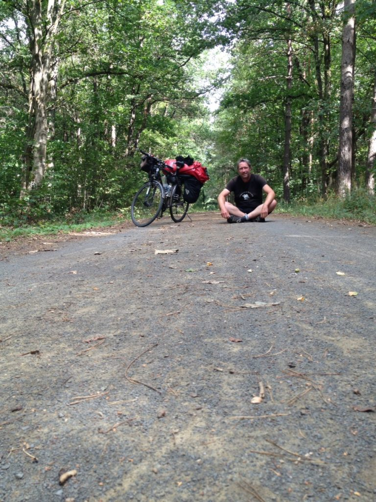 rechts neben einem bepackten Reiserad auf gerader Strecke im Wald sitzt ein Mann im Schneidersitz und schaut in die Kamera.