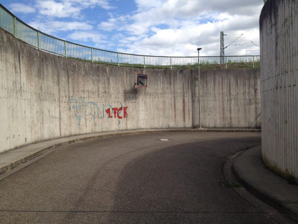 In einer runden Betonunterführung hänt ein Spiegel und an der Betonwand steht 1. FCK (Fußballverein Kaiserslautern)