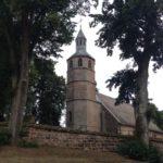 Achteckiger Sandstein Kirchturm gerahmt von Bäumen