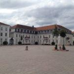Barocke Gebäude, weiß mit roten Walmdächern, zusammenhängend, verwinkelt vor weitem städtischem Platz